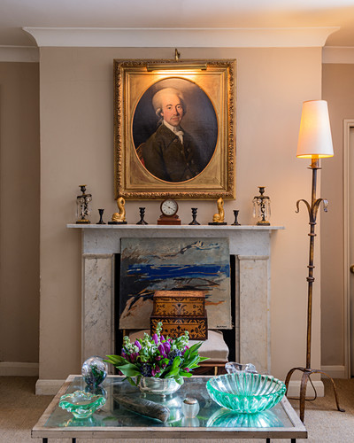 Antique portrait in gilt frame above fireplace in living room