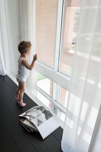 Kleiner Junge auf schwarzem Fußboden vor Fenster stehend