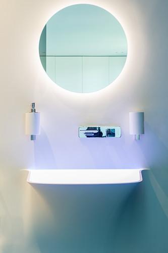 Designerbad mit rundem Spiegel und indirekter Beleuchtung