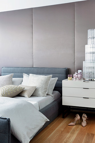 Graues Polsterbett vor gepolsterter Wand im glamourösen Schlafzimmer