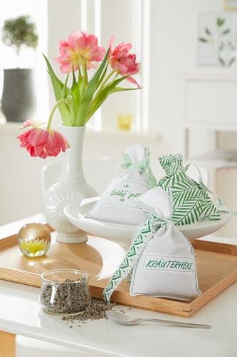 Handmade herbal sachets with green trim on tray