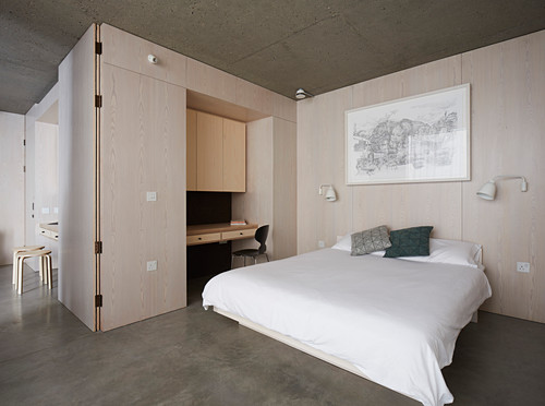 Double bed and wooden fitted furnishings in bedroom