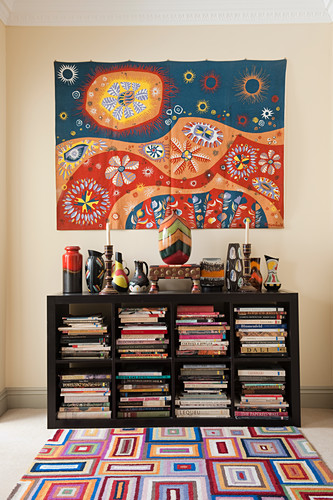 Mexican wall-hanging above collection of artistic vases on bookcase