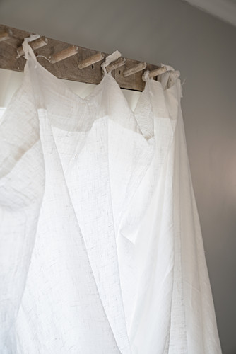 Linen curtain hung from wooden pegs