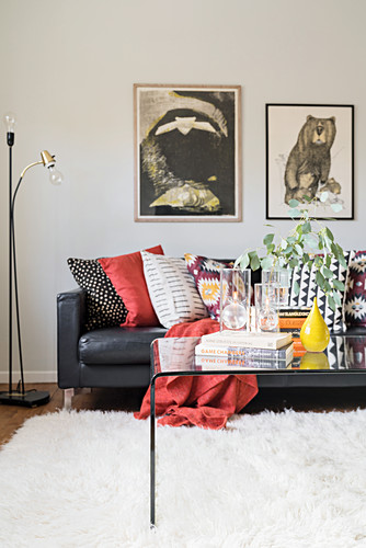 Colourful scatter cushions on leather sofa and glass table on white rug in living room