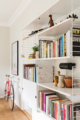 Books and ornaments on white shelves and bicycles in living room