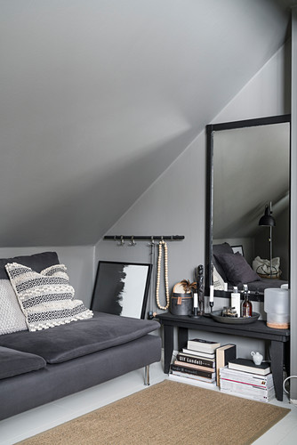 Sofa, side table and mirror on wall under grey, sloping ceiling