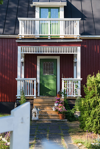 Falu-red Swedish house with green front door and veranda