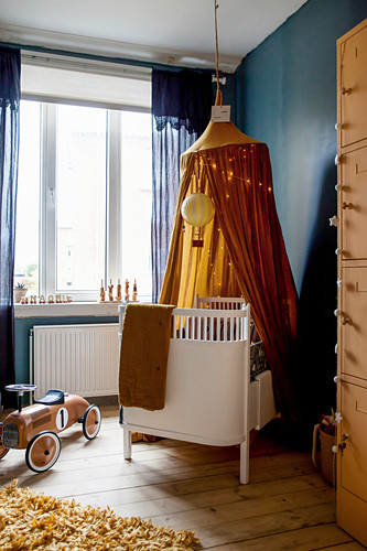Cot under ochre-yellow canopy against blue wall