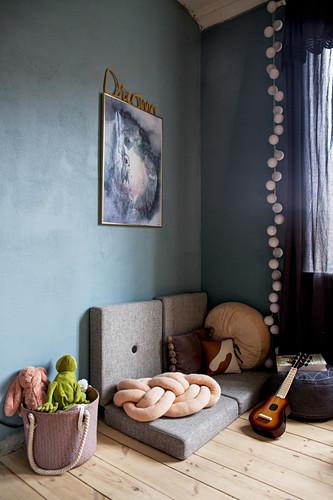 Folding mattresses and knotted cushion on wooden floor against blue wall