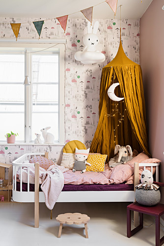 Mustard-yellow canopy above bed in little girl's bedroom
