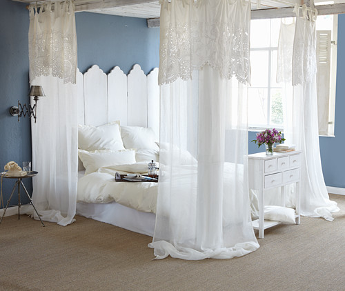 Blue walls and white four-poster bed in romantic bedroom