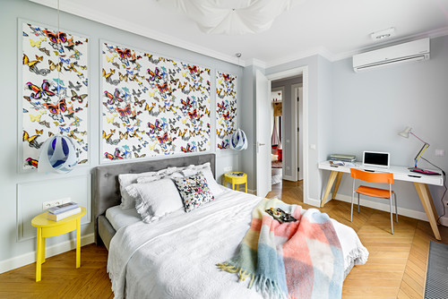 Butterfly wallpaper behind bed and desk in bedroom