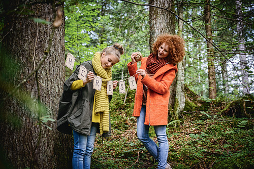 Girl and woman hanging up autumn garland in woods