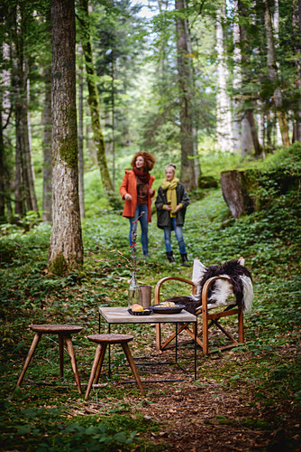 Girl and woman having autumnal picnic in woods