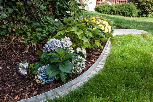 DIY metal and stone edging around flowerbed