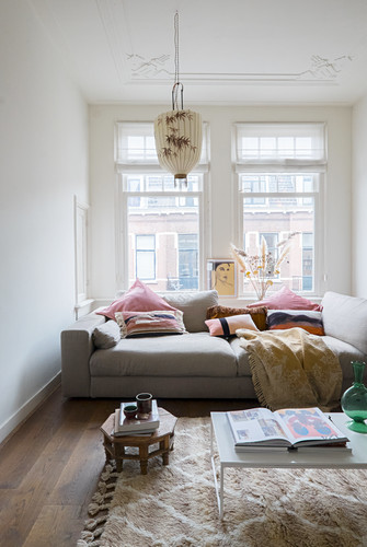 Cushions and blanket on couch below window in period apartment