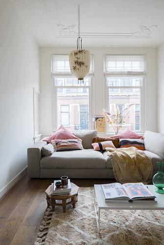 Schlafsofa mit Kissen und Decke vor Fenster in Altbauwohnung