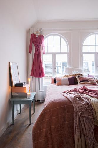Doppelbett mit Kissen und Tagesdecke vor Rundbogenfenstern im Schlafzimmer