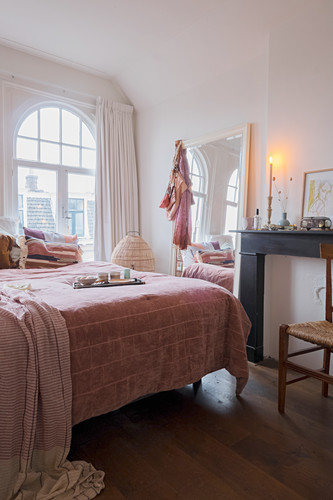 Double bed in front of arched windows, large mirror and disused fireplace in bedroom