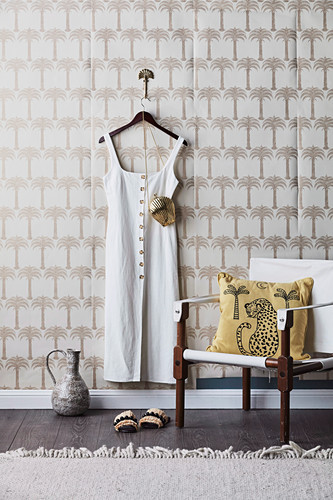 Dressing area with linen chair and linen dress on hooks in front of palm tree motif