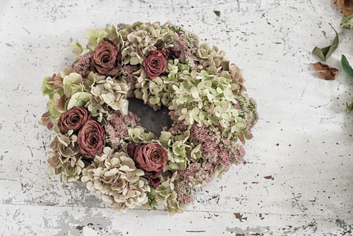 Handmade hydrangea and rose wreath on white shabby-chic table