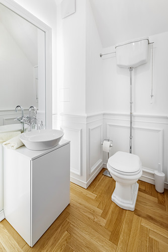 Washstand and toilet in white bathroom with parquet flooring