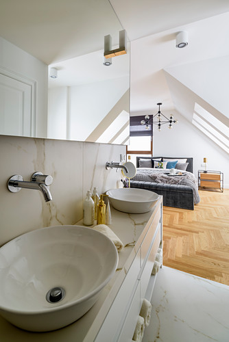 Marble washstand with countertop sinks in ensuite bathroom adjoining bedroom