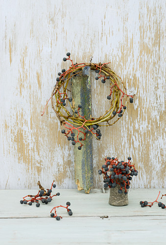 Braided wreath of Virginia creeper twigs and berries above small vase