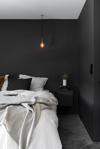 Bedroom with black walls and light bulb pendant lamp