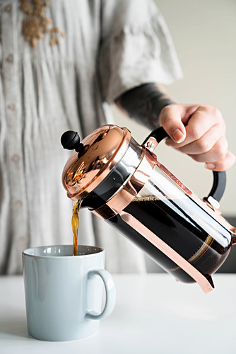 Pouring a cup of coffee from a French press