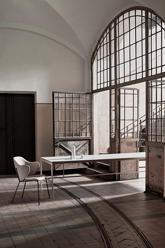 Long dining table in industrial building with vaulted ceiling and large arched doorway
