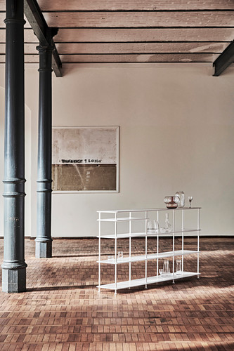 Delicate, modern shelves in old factory with metal pillars