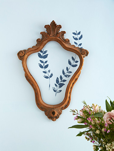 Leafy twigs printed on wall framed in old picture frame