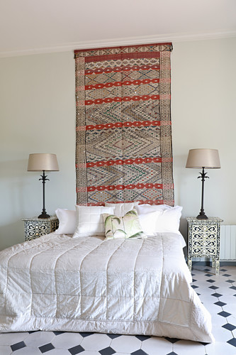 Oriental rug on wall above bed with quilted bedspread