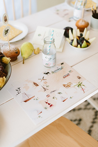 Table set with handmade place mats for child's birthday party with world travel motif