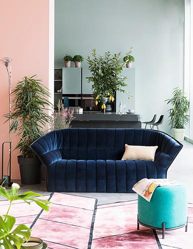 Dark blue velvet sofa in loft apartment with walls in pastel tones