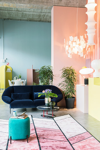 Collection of lamps in seating area of loft apartment with walls in pastel shades and exposed concrete ceiling