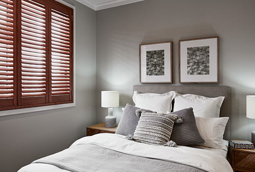 Bedroom in shades of grey and white with closed window shutters