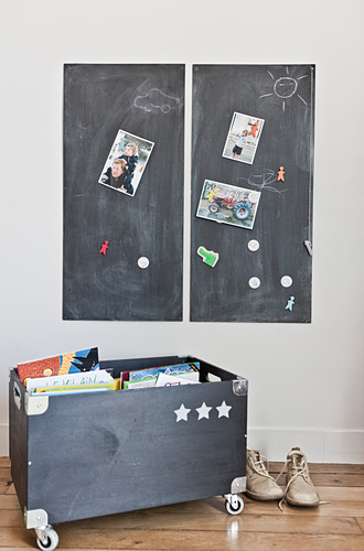 Zwei Tafeln an der Wand über einer Holzkiste mit Spielzeug