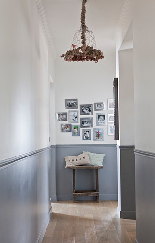 Two-tone walls in hallway with gallery of pictures at far end