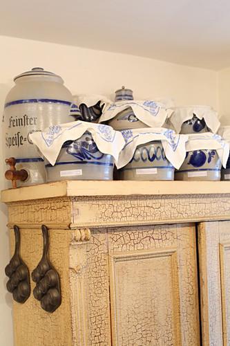 Old stoneware crockery on top of farmhouse cupboard
