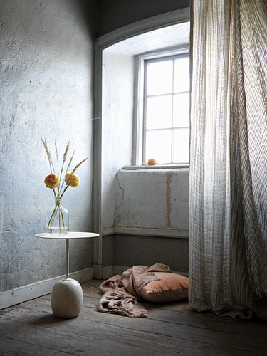 Flowers on side table, cushion on floor and curtain in corner of room