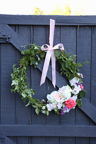 Wreath of leaves and flowers on wooden door