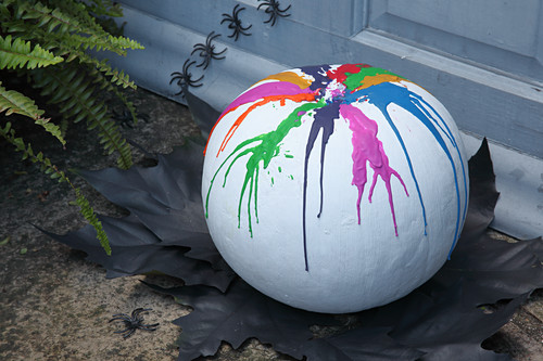 Handcrafted Halloween decoration: pumpkin painted white with colourful melted wax