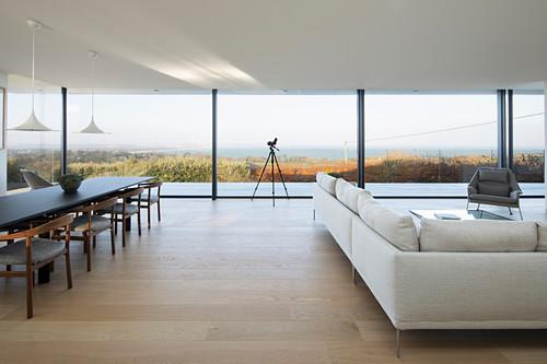 Helle Sofagarnitur und Essbereich vor raumhoher Verglasung in offenem Wohnraum