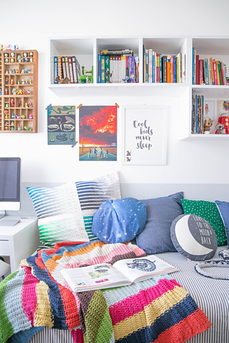 Colourful knitted blanket and cushions on bed below bookshelves