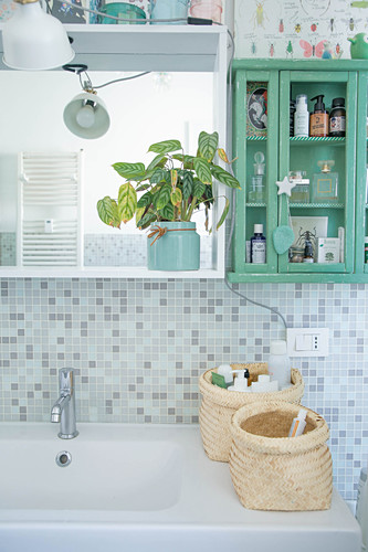 Baskets on sink below shelves and wall-mounted cabinet in bathroom