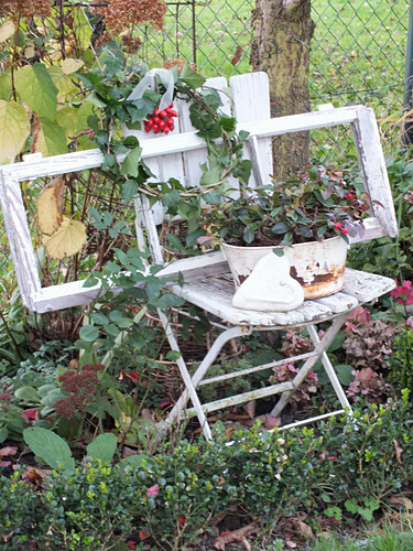 Window frame on old folding chair in autumnal garden