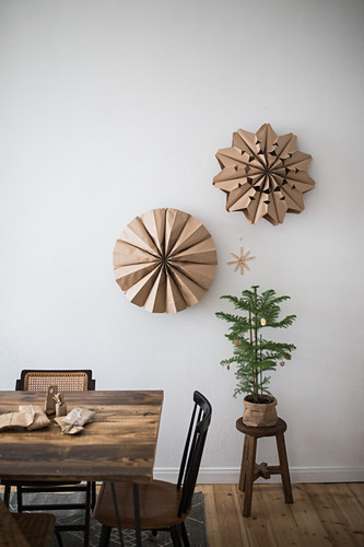 Decorations handmade from brown paper on wall above tiny fir tree in dining room